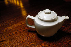 Teapot on old wooden table against the background of dark room Royalty Free Stock Images