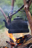 Teapot Over Campfire. Boiling water in Hanging Tea kettle over an open flame during a Nature Hiking or Expedition stock photo