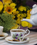 Teapot pouring into cup. Fine china tea cup with thistle design being filled from teapot, yellow flowers in background stock photography