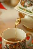 Teapot pouring tea Royalty Free Stock Image