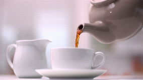 Teapot pouring tea into cup Stock Photography