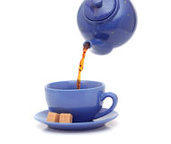 Teapot pouring tea into a cup Royalty Free Stock Photos