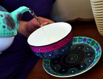 Teapot pouring tea into a tea cup. A colourfully patterned teapot pouring tea into a colourfully patterned teacup, hovering over a matching saucer Royalty Free Stock Photos