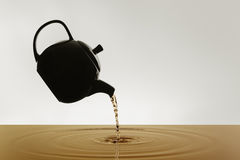Teapot silhouette pouring tea Stock Photo