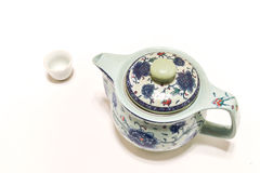 Teapot and a Small cup. On a white background Royalty Free Stock Photo