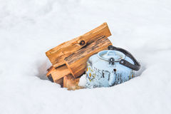 Teapot on snow. Kettle and firewood in the background of white snow Royalty Free Stock Photography