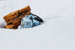 Teapot on snow. Kettle and firewood in the background of white snow Royalty Free Stock Images