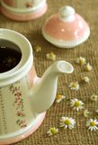 Teapot with soothing herbal chamomile tea. Royalty Free Stock Image