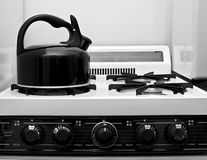 Teapot and stove. Teapot sits on vintage stove in this black and white image of a kitchen Stock Photo