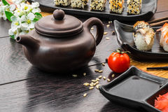 Teapot and sushi set sashimi and sushi rolls on dark background. Teapot and sushi set sashimi, nigiri, maguro and sushi rolls served on plate and white flowers stock photography