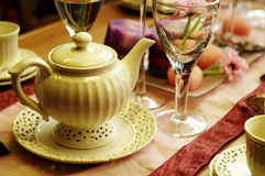 Teapot and table setting. Teapot and decorated table setting Royalty Free Stock Image