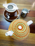 Teapot with tea cozy, tea cup and a jug of milk Royalty Free Stock Image