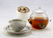 Teapot with tea, cup on a saucer and sugar bowl with brown and w Stock Photos