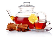 Teapot and tea in cup with spices and lemon Royalty Free Stock Photos