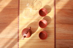 Teapot,tea cup and tea leaves on a bamboo mat. Stock Photos