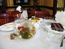 Teapot with tea and dessert on the table in the cafe photo Stock Photo
