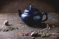 Teapot and tea leaves Stock Photos