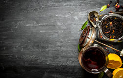 Teapot with tea and lemon. On a black wooden background Stock Image