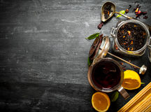 Teapot with tea and lemon. On a black wooden background Stock Images