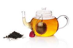 Teapot with teaball and black tea. Isolated on white Stock Photos