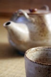 Teapot and teacup. Teacup in the foreground and teapot in the background. Focus is on the cup. The style of cup and teapot is traditional Japanese pottery Royalty Free Stock Images