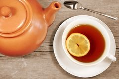 Teapot and teacup on grunge wooden table Stock Image