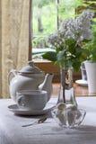 Teapot, teacup and lilacs Stock Image