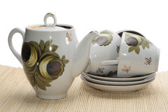 Teapot with three cups. On the mat Royalty Free Stock Image