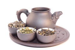 Teapot and three cups of herbal tea. Close-up, isolated on white Royalty Free Stock Image