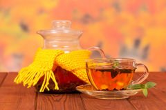 Teapot tied with yellow scarf and cup of tea Stock Photo