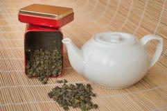 Teapot and a tin of traditional Asian green tea loose Stock Photos