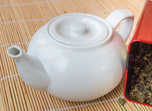 Teapot and a tin of traditional Asian green tea loose Royalty Free Stock Image