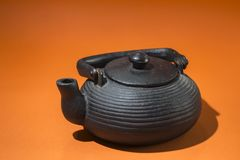 Teapot, tradition, iron, east, craftsmanship, orange, tea, flavor, black, metal, drink, vintage, ceremony, kitchen, utensil,. View of an oriental iron black stock images