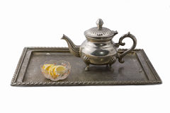 Teapot on a tray. A retro steel teapot on a tray served with lemon slices in  glass bowl Royalty Free Stock Image