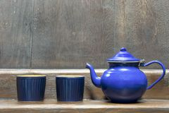 Teapot with two blue cups. On a wooden shelf Royalty Free Stock Photography