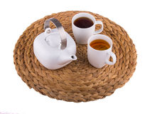 A teapot and two cups on a straw Mat. Stock Photo