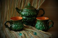 Teapot and two mugs. Green teapot and two mugs on a striped background Stock Photography