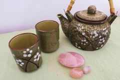 Teapot and two tea cups with rose quartz stones royalty free stock photography