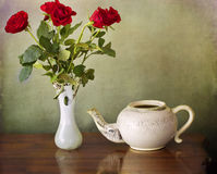 Teapot and vase with red roses Royalty Free Stock Photo