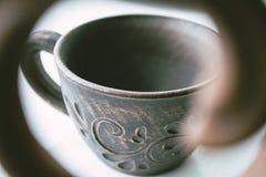 Teapot w przedpolu i filiżanka glina stojak blisko okno obraz stock
