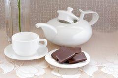 Teapoten kuper och choklad på en plätera royaltyfri foto