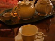 Teapots and cup of tea. With two little cakes stock footage