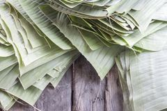 Tear off the banana leaf, stack it on the wooden table. royalty free stock photography