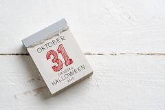 Tear-off calendar with october 31st, date of Halloween, on top. In German Stock Photo
