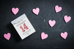 Tear-off calendar surrounded by hearts with 14th of february on top. On a slate background royalty free stock photography