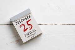 Tear-off calendar with 25th of december on top. On a wooden surface Royalty Free Stock Images