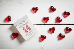 Tear-off calendar with 14th of february on top. Surrounded by hearts on a wooden surface stock images