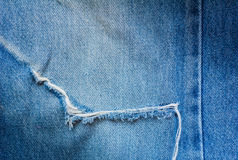 Tear in old blue jeans Stock Photo