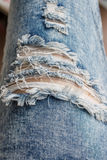 Tear in old worn out jeans Royalty Free Stock Photos