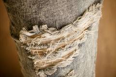 Tear in old worn out jeans Royalty Free Stock Image